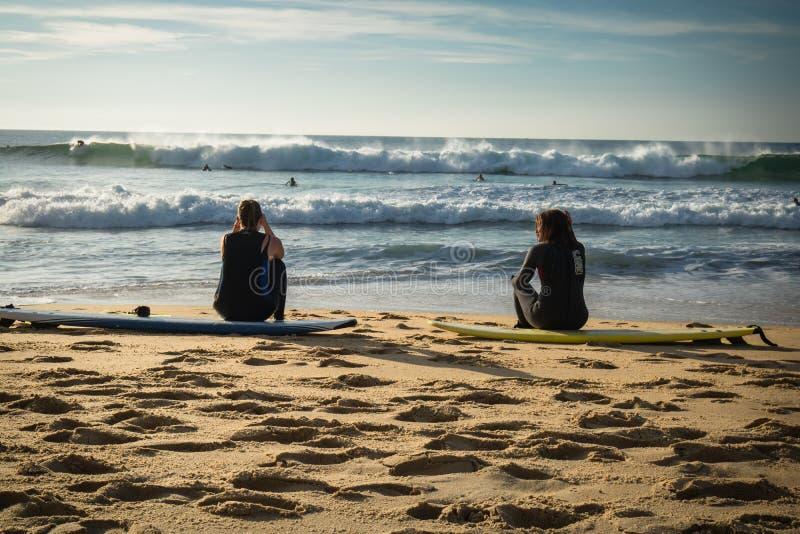Capbreton, France - October 4, 2017: back view of women girls surfers sitting on sandy beach on surfboard royalty free stock photos