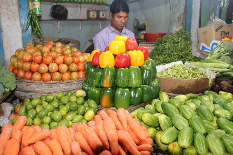 Capciam doux, poivre de Chili Red Green Yellow Sweet dans la boutique végétale bangladaise avec le gardien de boutique photos libres de droits