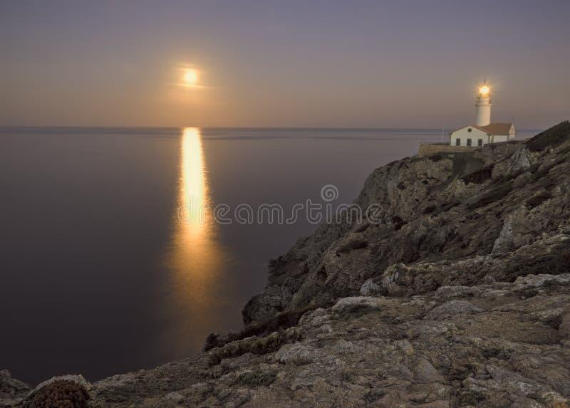 Capdepera-Leuchtturm an der Dämmerung, mit Mondstrahl auf Meer und Felsen, Mallorca, Spanien stockbilder