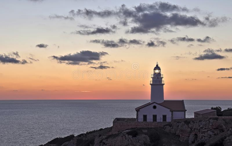 Capdepera lighthouse at dawn with beacon, rocky foreground, and dramatic beautiful sky, cala ratjada, mallorca, spain. Capdepera lighthouse at sunrise with light royalty free stock photos