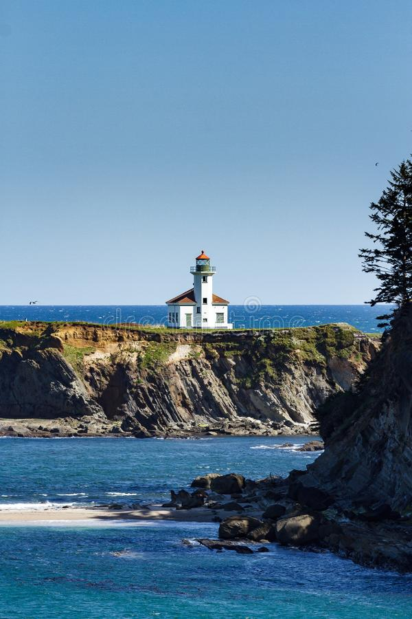 Cape Arago Lighthouse on the Pacific Coast of Oregon. Rock Cliffs, Blue Water and the Cape Arago Lighthouse on the Picturesque Pacific Coast of Oregon royalty free stock photography