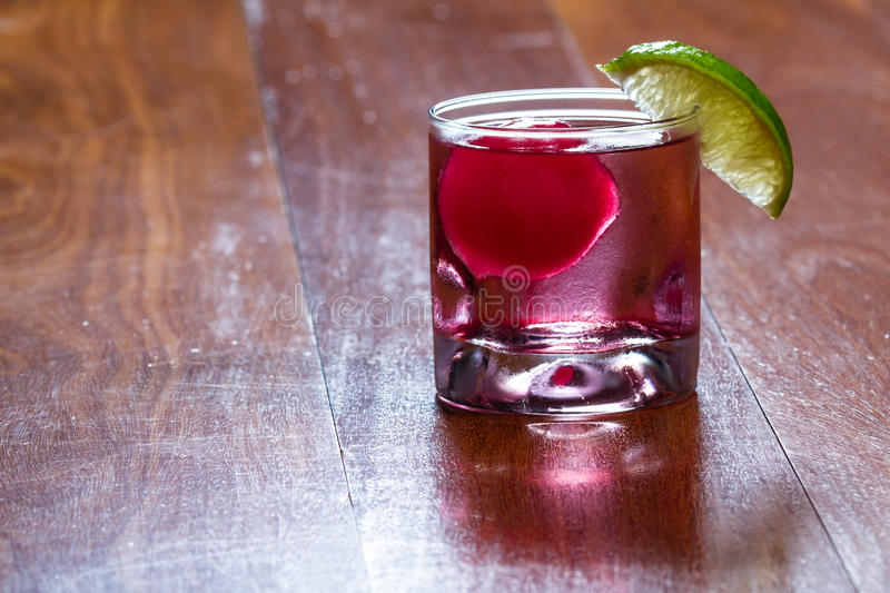 Cape cod cocktail. Refreshing drink with a red ice ball releasing flavor into the cocktail as it melts and chills the beverage garnished with a lime wedge on the royalty free stock photography
