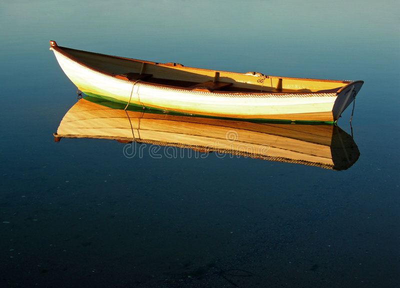 Cape Cod Dory Reflection. An old style row boat is mirrored in the waters of Stage Harbor at Chatham, Massachusetts royalty free stock photography