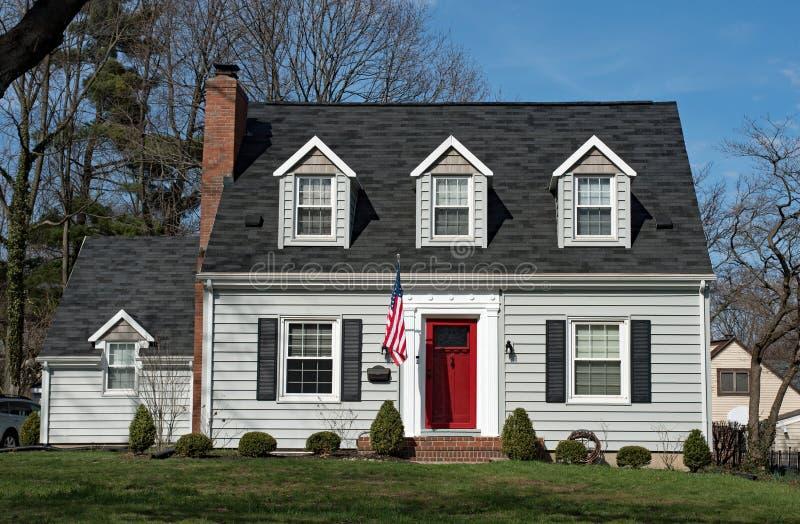 Cape Cod hus med tre vindskupefönster & den röda dörren arkivbilder