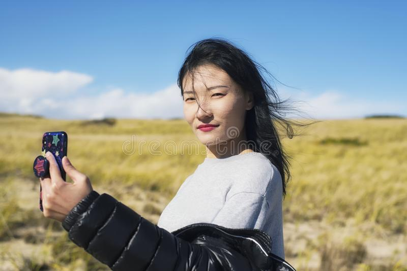 Cape Cod National Seashore Nature woman selfie. A chinese woman taking a selfie on a sunny windy day on the cape cod national seashore in Truro Massachusetts royalty free stock images