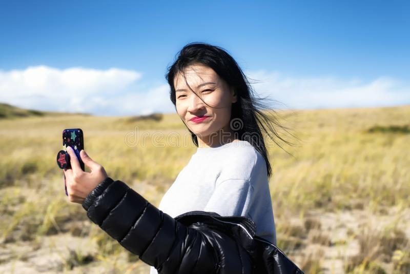Cape Cod National Seashore Nature woman selfie. A chinese woman taking a selfie on a sunny windy day on the cape cod national seashore in Truro Massachusetts stock photos