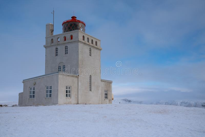 Cape Dyrholaey lighthouse, Vik, Iceland. Panoramic image of the lighthouse of Cape Dyrholaey with snow and early morning light, winter in Iceland stock images