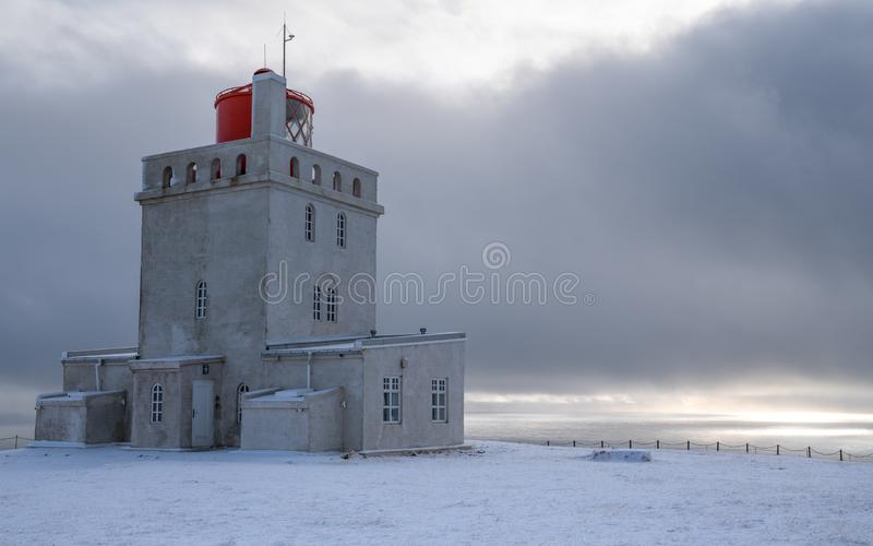 Cape Dyrholaey lighthouse, Vik, Iceland. Panoramic image of the lighthouse of Cape Dyrholaey with snow and early morning light, winter in Iceland stock image