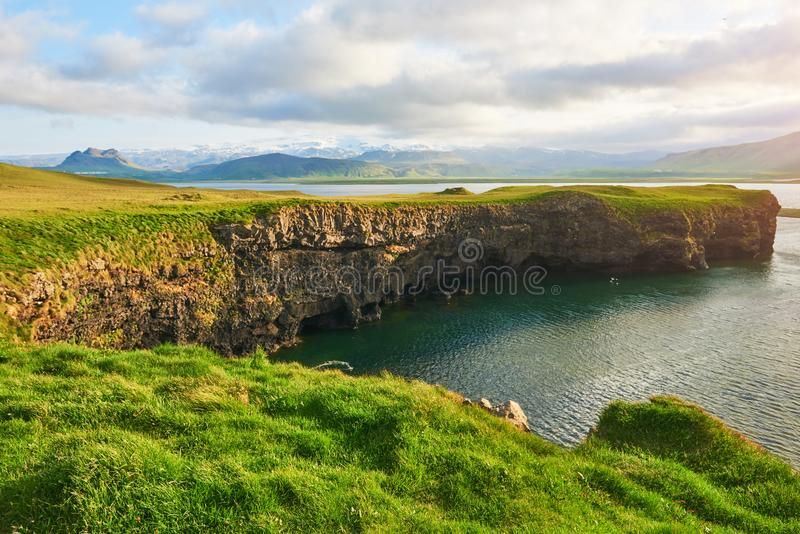 Cape Dyrholaey at southern Iceland. Altitude 120 m, and mean hill island with a door opening stock photos