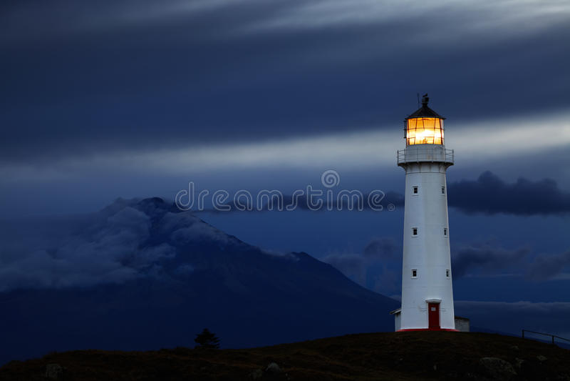 Cape Egmont Lighthouse, New Zealand. Cape Egmont Lighthouse and Taranaki Mount on background, New Zealand stock photos