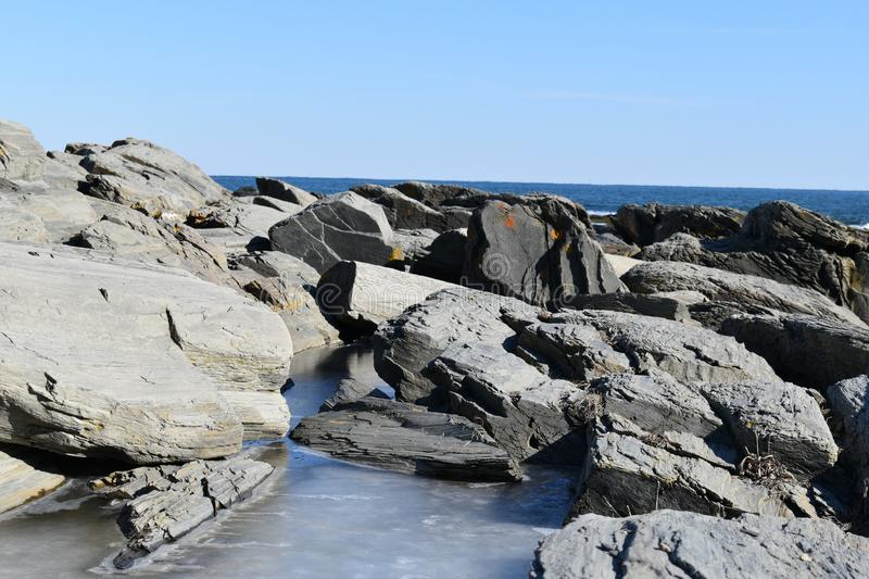 Cape Elizabeth`s rocky and partially frozen shoreline on Cape Elizabeth, Cumberland County, Maine, New England Lighthouse, US. A clear cold winter day along the stock image
