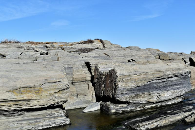 Cape Elizabeth`s rocky shoreline on Cape Elizabeth, Cumberland County, Maine, New England, US. A clear sunny cold winter day along the rocky shoreline at Dyer royalty free stock photo