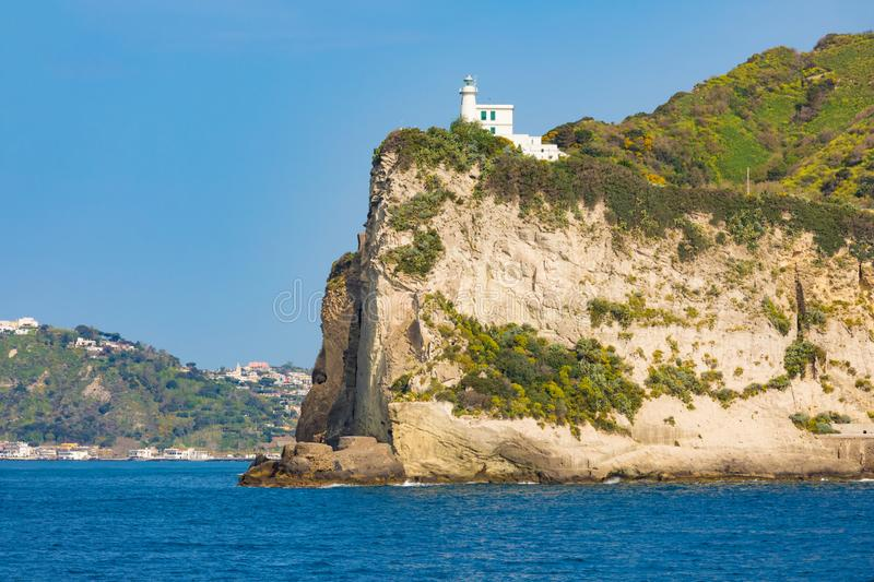 Cape Miseno Lighthouse, Gulf of Naples, Italy in sunny summer da. Cape Miseno Lighthouse on high rock in deep blue sea, Gulf of Naples, Italy in sunny summer day stock photos