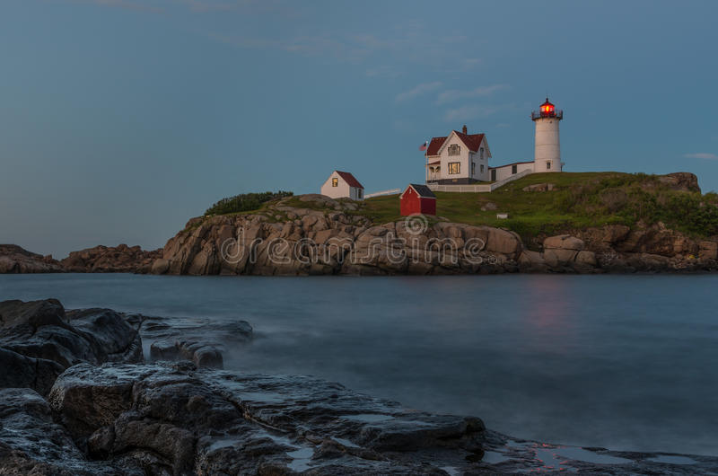 Cape Neddick Lighthouse. In York, Maine at dusk. Located along the Atlantic Ocean the ocean waves were blurred by a timed exposure stock photo