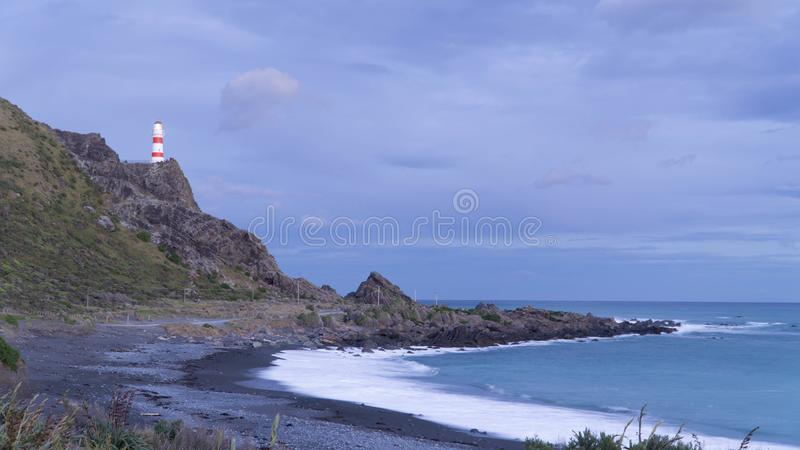 Cape Palliser Lighthouse locatedcon the top of rocky cliff in the end of the day, New Zealand royalty free stock photo