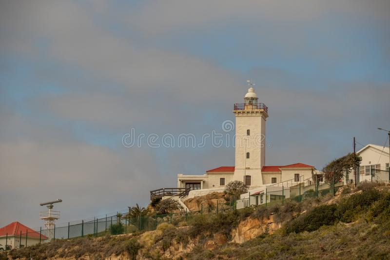 Cape St Blaize lighthouse in Mossel Bay South Africa. Mossel Bay, South Africa - August 16, 2019: the Cape St Blaize lighthouse on a hill above the coastal town stock images