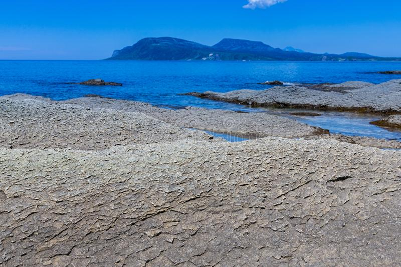 Cape Stolbchaty. Cape on the west coast of the island of Kunashir. It is composed of layers of basaltic lavas of the Mendeleyev v royalty free stock image