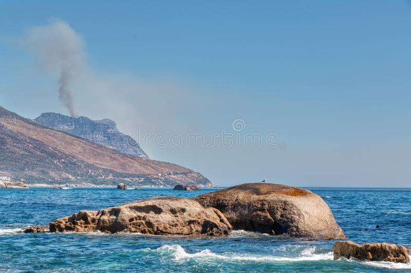 Cape Town coastline with a fire in the far background. Cape Town, South Africa: Coastline drought stricken with a fire in the far background royalty free stock photo