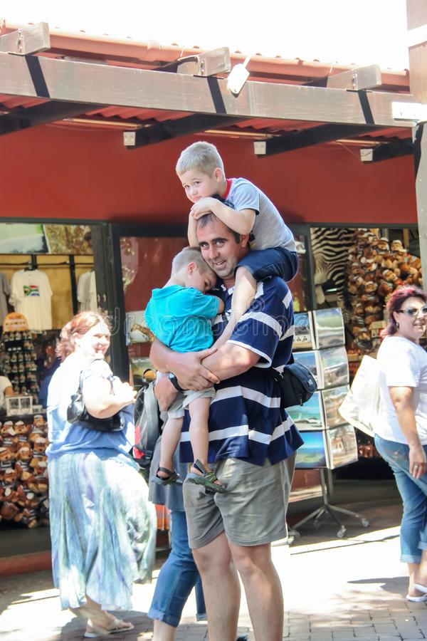 Cape Town - 2011: A daddy holds on tight to his kids stock image