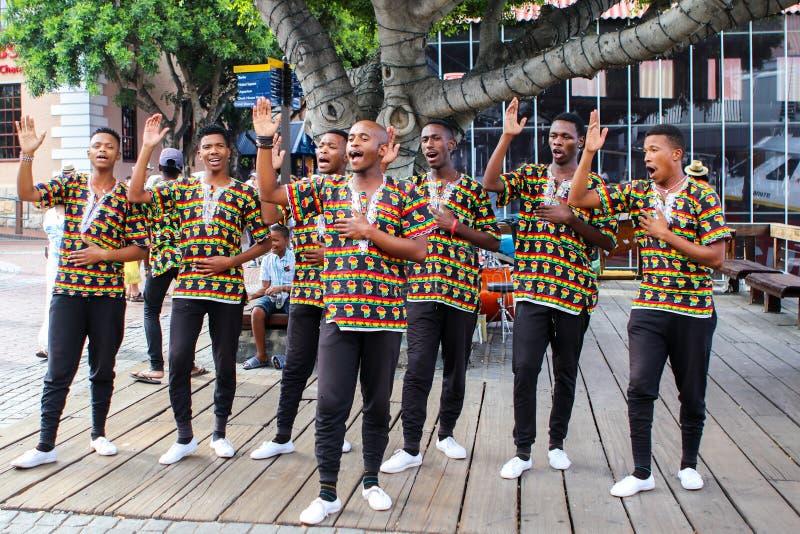 CAPE TOWN, SUDAFRICA - 23 DICEMBRE 2017: gruppo di giovani in costumi africani nazionali che ballano e che cantano fotografie stock