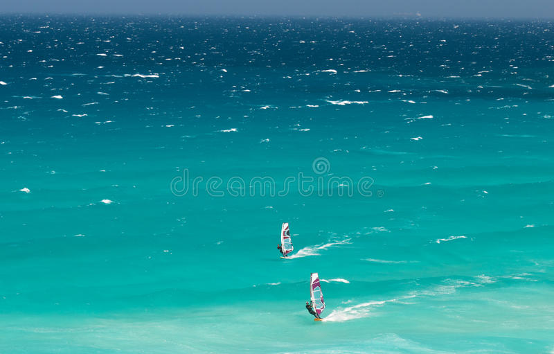 Cape Town Windsurfers. South Africa,Cape Town,28 February 2011:Two windsurfers enjoy the unseasonal windy conditions in the Atlantic Ocean at Scarborough off the stock photography