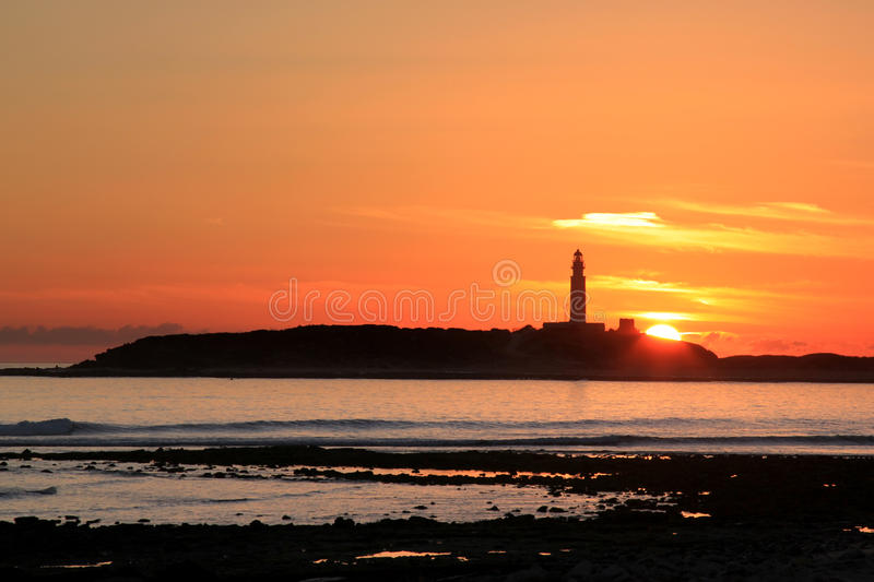 Cape Trafalgar Lighthouse and sunset, Spain. Cape (Cabo) Trafalgar is a peninsula, an offshore rock connected to the land by a sand spit. Cape Trafalgar is royalty free stock photos