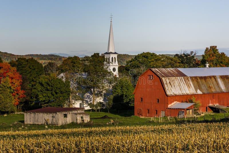 Capela branca, celeiros vermelhos e campos de exploração agrícola no por do sol - Peacham, Vermont imagens de stock
