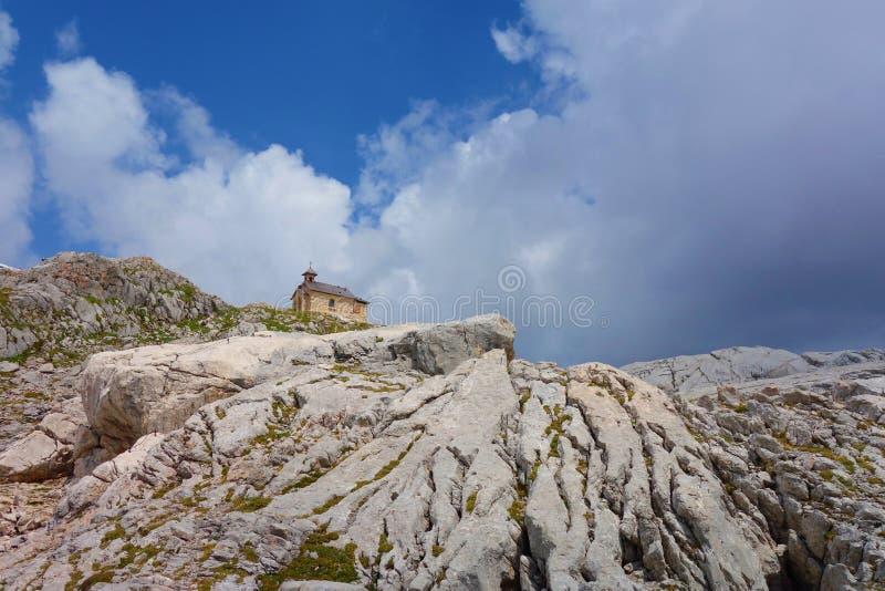 A capela da montanha localizou próximo a Simonhytutte oposto à geleira de Dachstein, em cumes austríacos durante o verão, região  imagens de stock royalty free