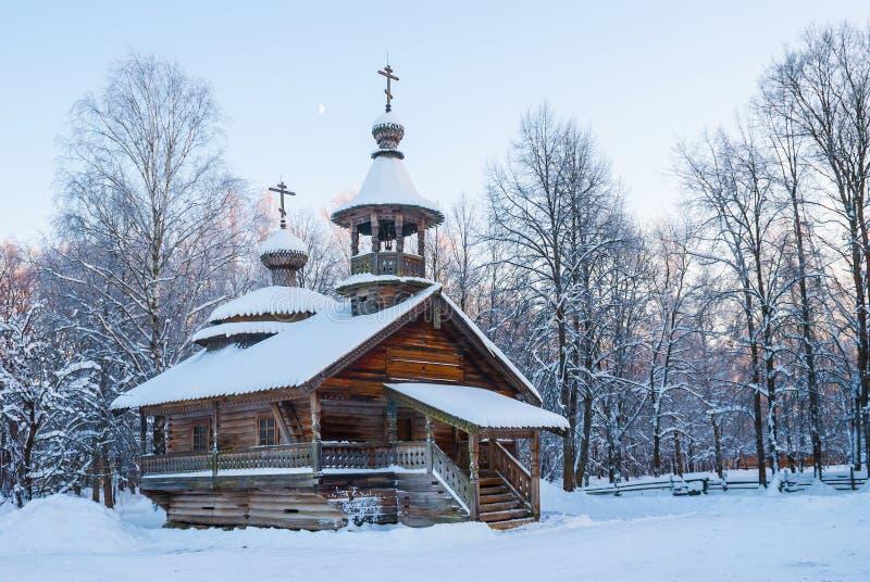 Capela de madeira na floresta nevado do inverno no por do sol imagem de stock