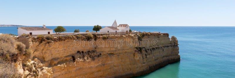 Capela de Nossa Senhora a Dinamarca Rocha sobre os penhascos espetaculares em Nova Beach O Algarve imagens de stock
