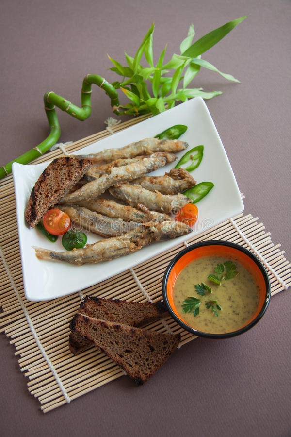 Capelin. Fish fried in batter with sauce stock photos