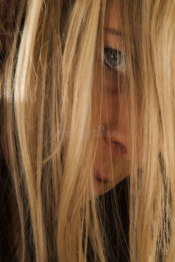 Capelli biondi di fine della donna davanti al fronte serio immagine stock