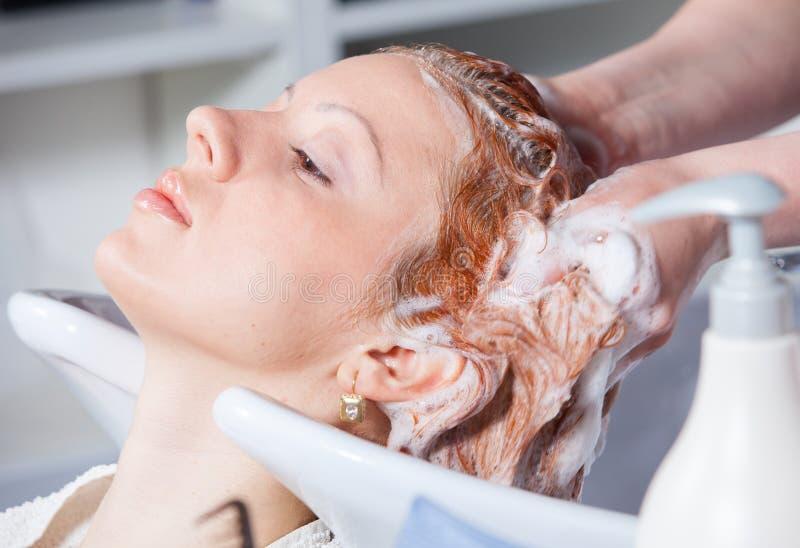 Capelli che lavano ad un salone di lavoro di parrucchiere immagine stock
