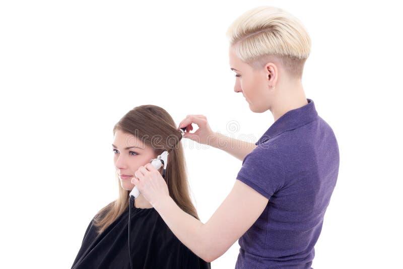 Capelli d'arricciatura del parrucchiere femminile al giovane bello isolato della donna fotografia stock