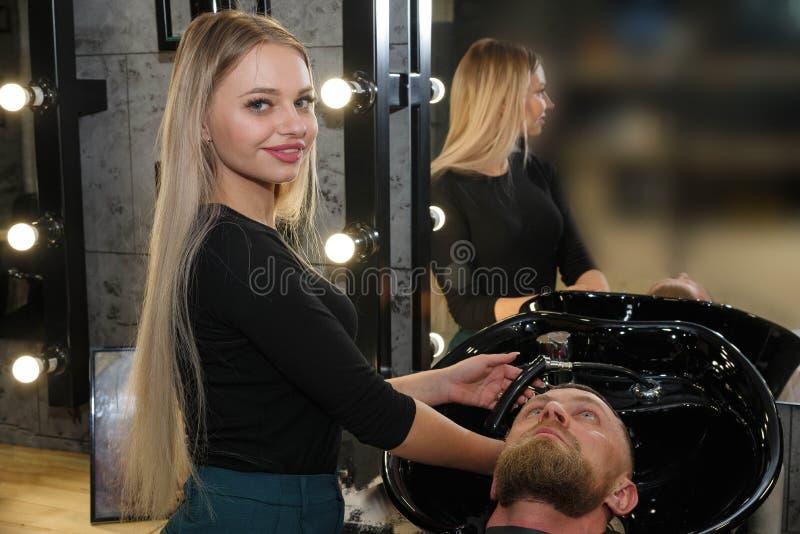 Capelli del ` s del cliente di lavaggio del parrucchiere nel negozio di barbiere fotografia stock libera da diritti