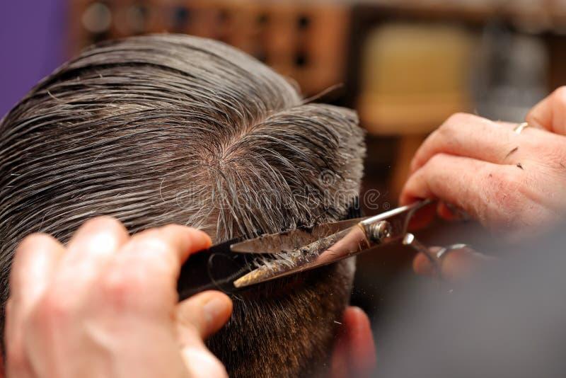 Capelli della guarnizione del parrucchiere con le forbici immagini stock