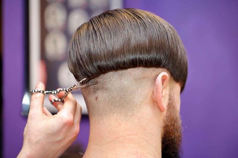 Capelli della guarnizione del parrucchiere con le forbici fotografie stock