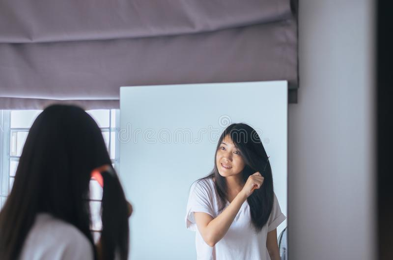 Capelli di secchezza della donna asiatica con l'asciugamano, essiccazione femminile i suoi capelli lunghi con il pettine fotografia stock libera da diritti