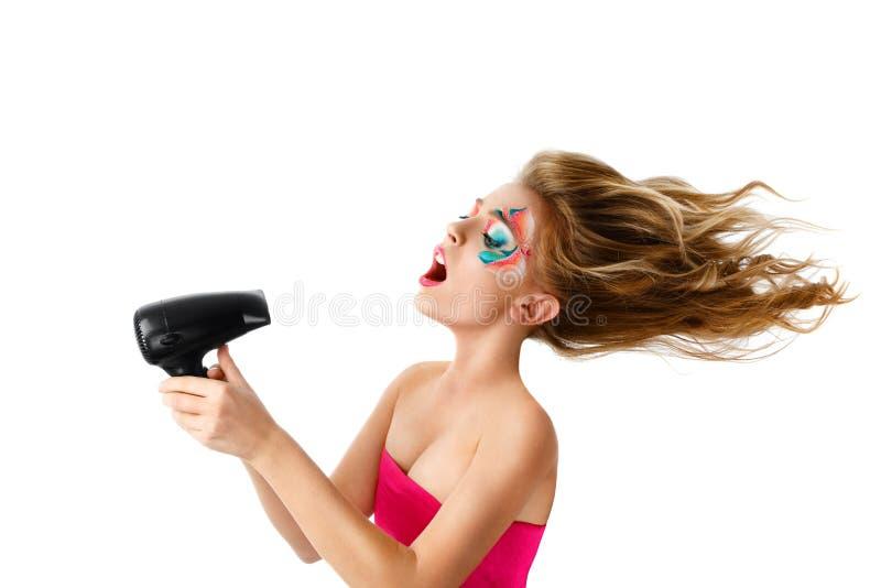 Capelli di secchezza della donna con il ventilatore fotografia stock