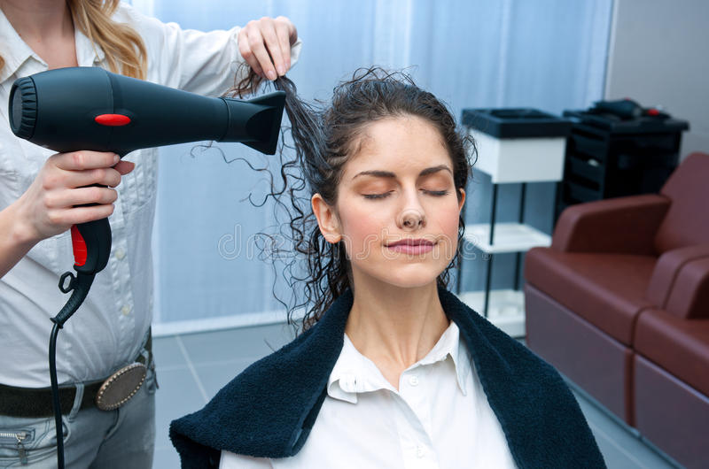 Capelli di secchezza della donna dello stilista in salone fotografie stock libere da diritti