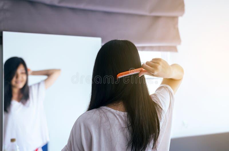Capelli di secchezza della giovane donna asiatica con l'asciugamano, essiccazione femminile i suoi capelli lunghi con il pettine fotografia stock