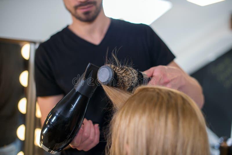 Capelli di secchezza della giovane donna di OS del parrucchiere fotografia stock