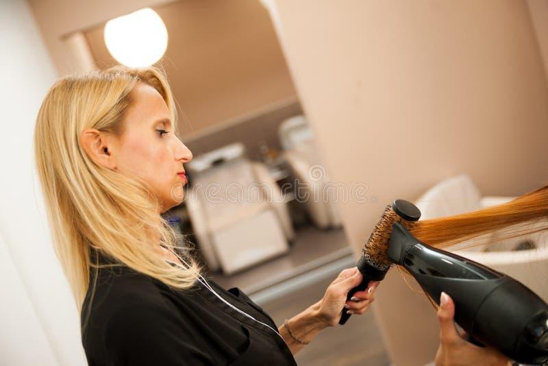 Capelli di secchezza di un cliente femminile al salone di bellezza - hai dello stilista fotografia stock