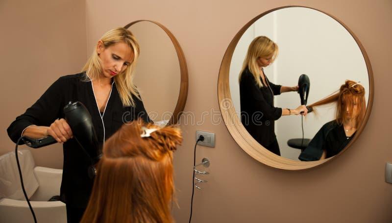 Capelli di secchezza di un cliente femminile al salone di bellezza - hai dello stilista immagini stock libere da diritti