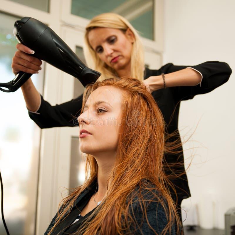 Capelli di secchezza di un cliente femminile al salone di bellezza - hai dello stilista fotografia stock libera da diritti