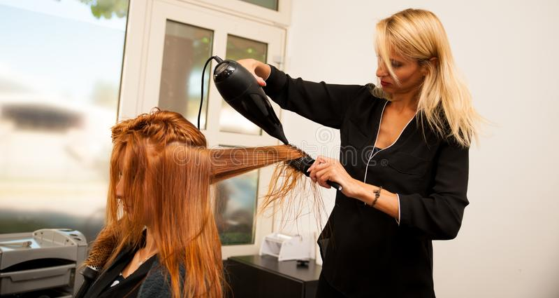 Capelli di secchezza di un cliente femminile al salone di bellezza - hai dello stilista immagine stock libera da diritti