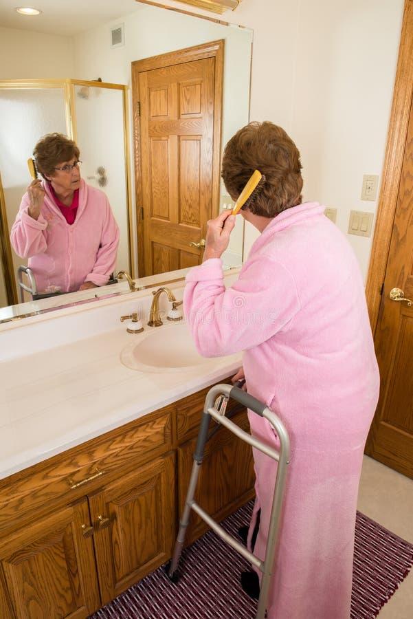 Capelli di spazzolatura della donna senior anziana immagini stock
