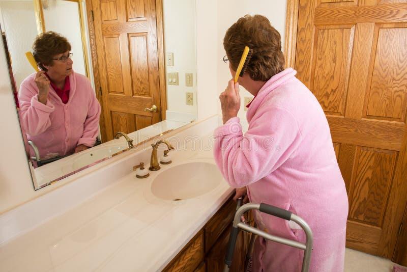 Capelli di spazzolatura della donna senior anziana fotografia stock libera da diritti