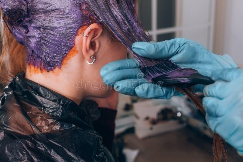 Capelli di tintura del parrucchiere professionista del suo cliente in salone Fuoco selettivo fotografia stock libera da diritti