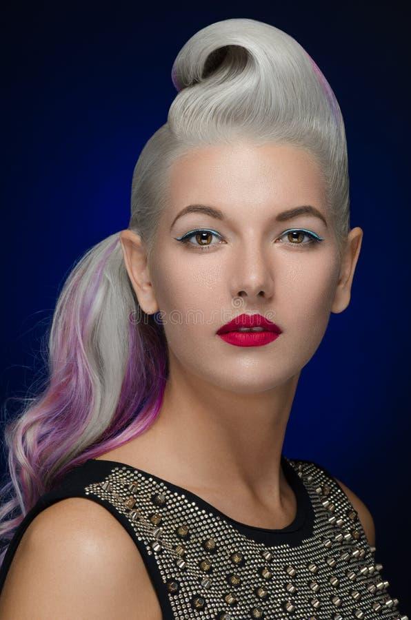 Capelli e tema di trucco: bella giovane donna bionda con capelli creativi che disegnano con le labbra rosse su un fondo blu scuro immagini stock